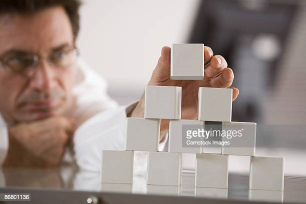 Businessman stacking blocks