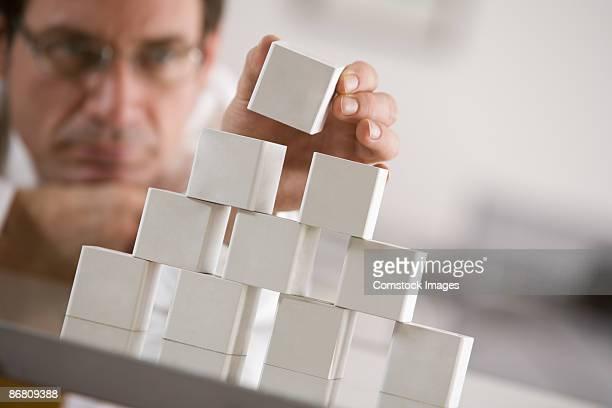 Businessman stacking blocks