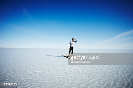 Businessman standing alone on life raft