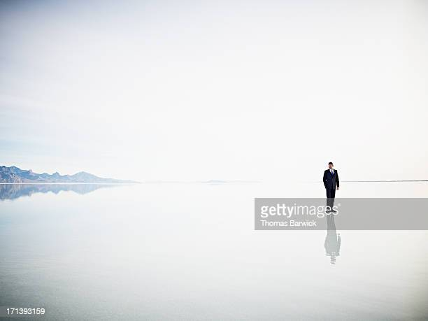 Businessman standing alone on surface of calm lake