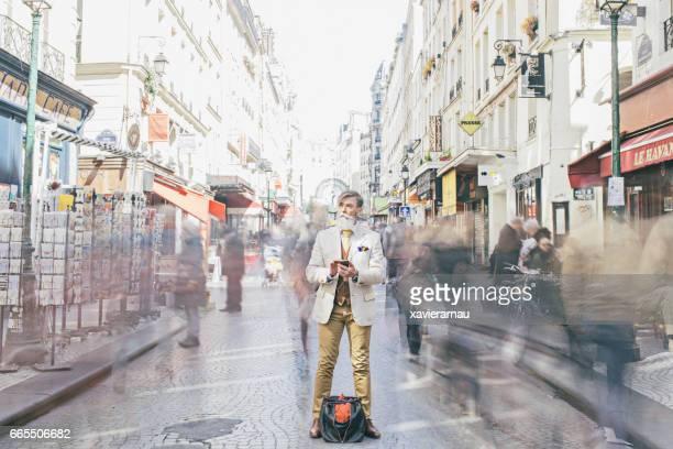 Homme d'affaires, debout au milieu de la foule se déplaçant sur la rue
