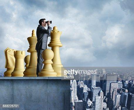 Businessman standing among chess pieces looks through binoculars