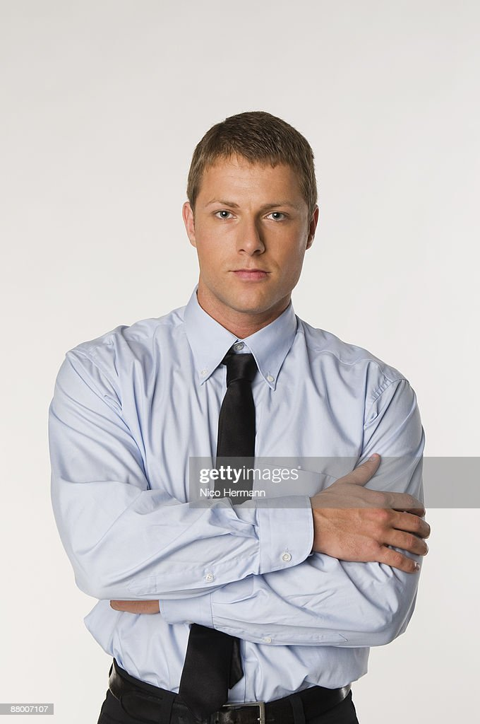 Businessman with arms crossed, portrait, close-up : Stock Photo