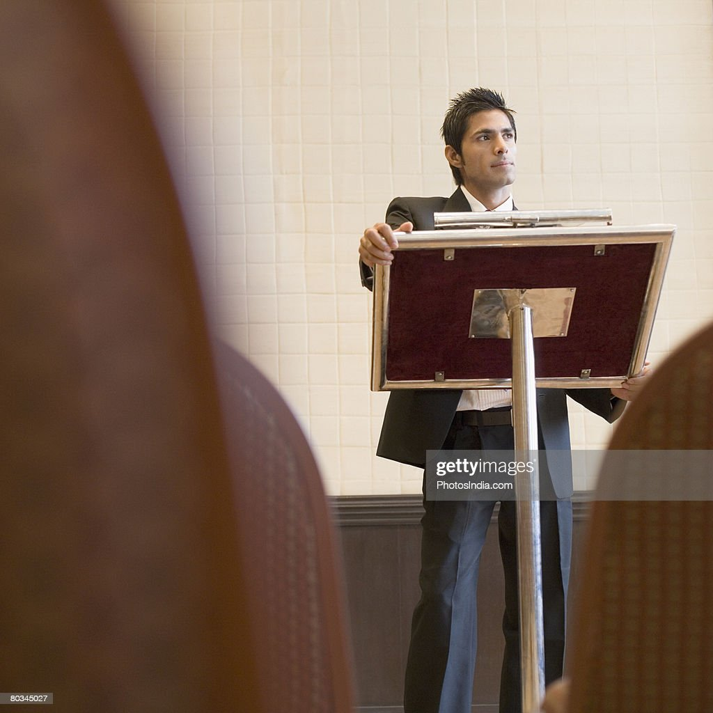 Businessman standing at a podium and looking away : Stock Photo
