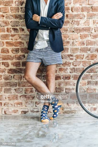 Businessman standing at brick wall wearing jacket and underwear