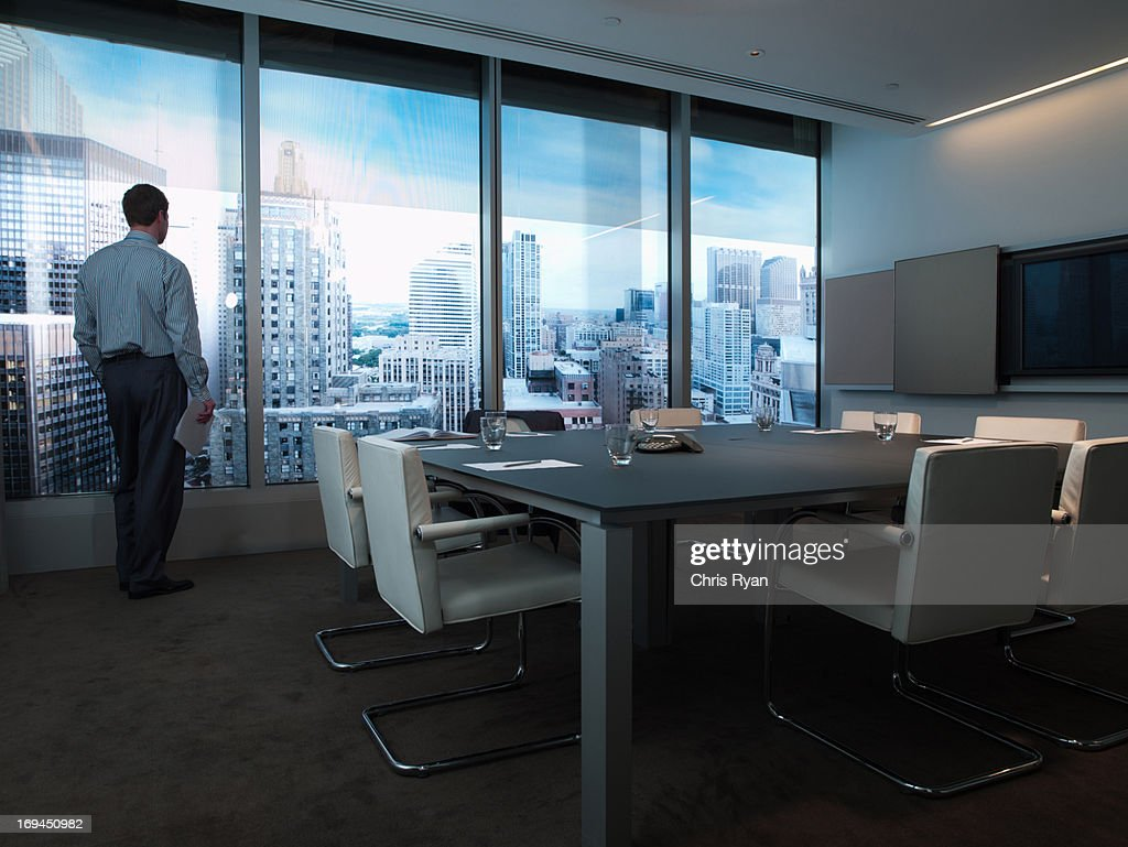 Businessman standing at conference room window overlooking city : Stock Photo