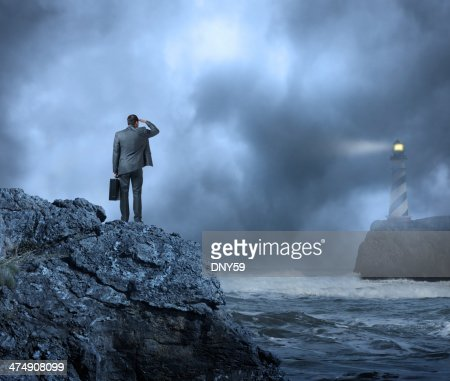 Businessman standing at edge of water looking towards a lighthouse