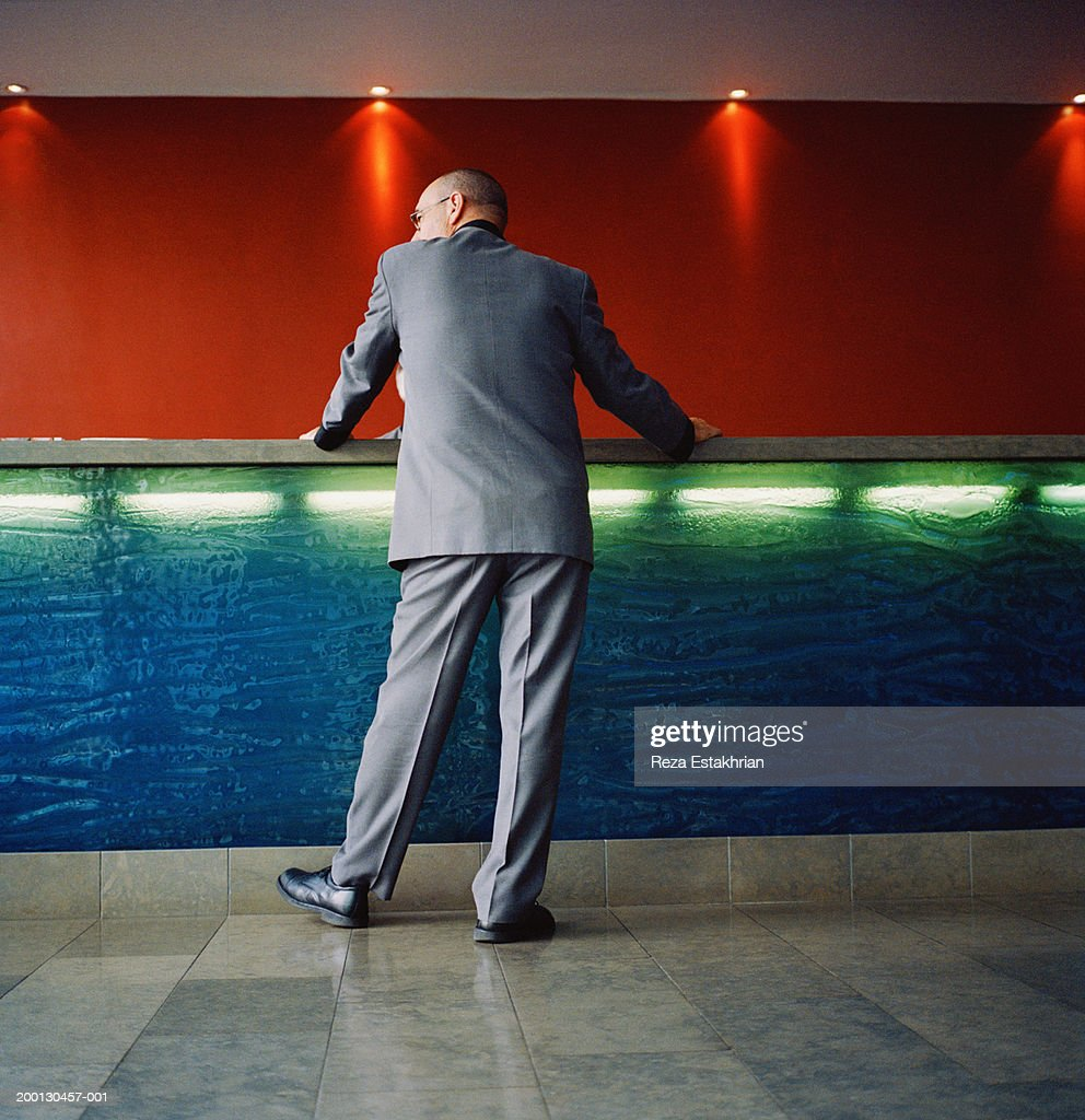 Businessman standing at hotel front desk, low angle view : Stock Photo