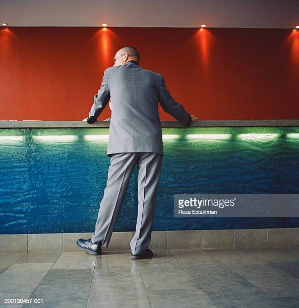 Businessman standing at hotel front desk, low angle view