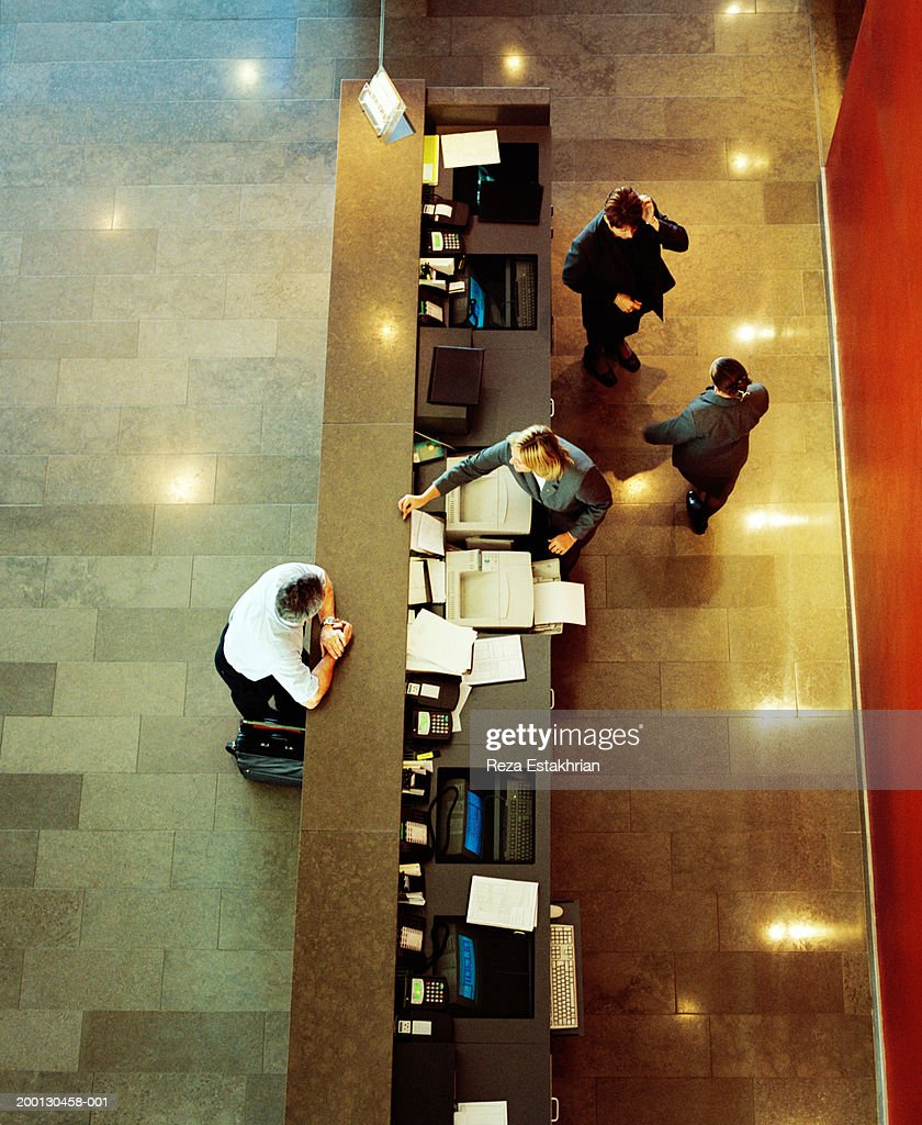 Businessman standing at hotel reception desk, overhead view : Stock Photo