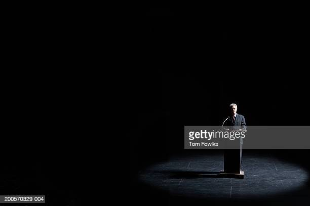 Businessman standing at podium illuminated by spotlight, elevated view