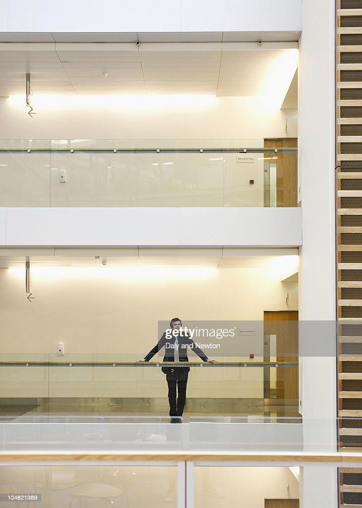 Businessman standing at railing in corridor : Stock Photo