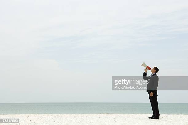 Businessman standing at the beach shouting into megaphone