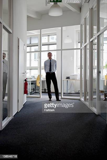 A businessman standing at the end of a corridor