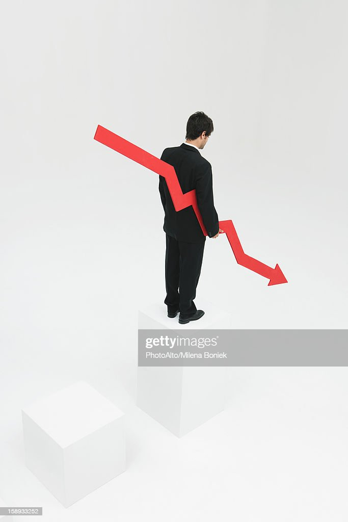Businessman standing at top of steps holding arrow pointed downward : Stock Photo
