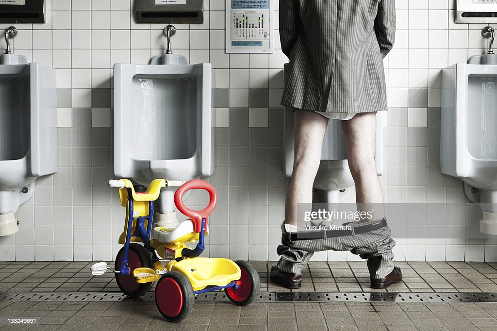 Businessman standing at urinal with his tricycle : Stock Photo