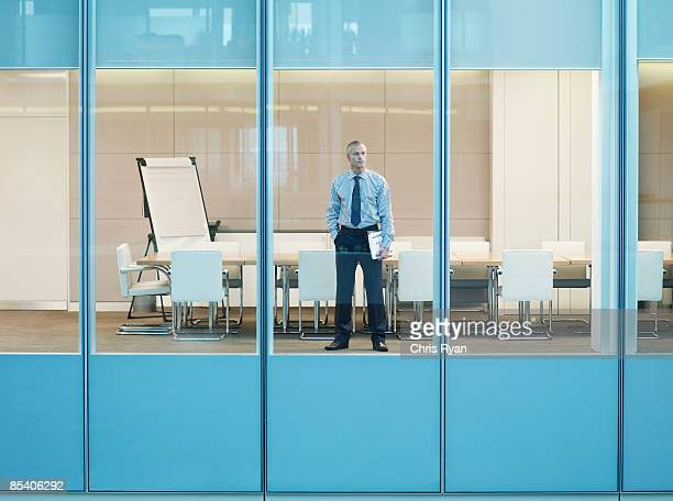 Businessman standing at window in conference room
