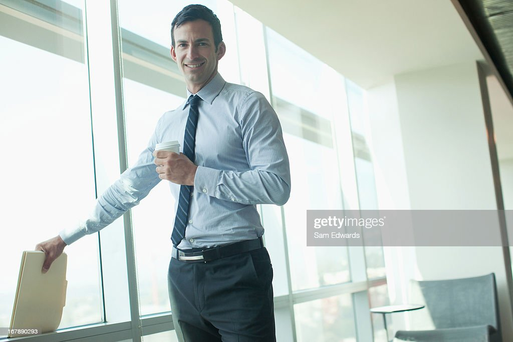 Businessman standing at window in office : Stock Photo