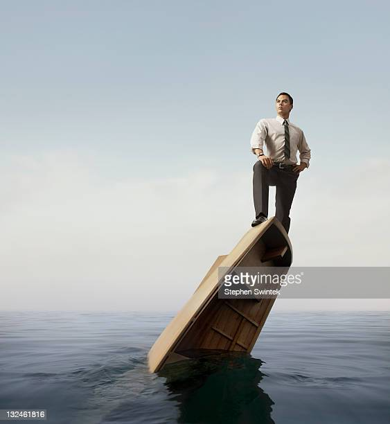 businessman standing atop a sinking boat