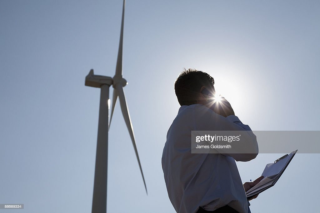 Businessman standing beneath wind turbine : Stock Photo