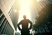 Businessman standing between city buildings