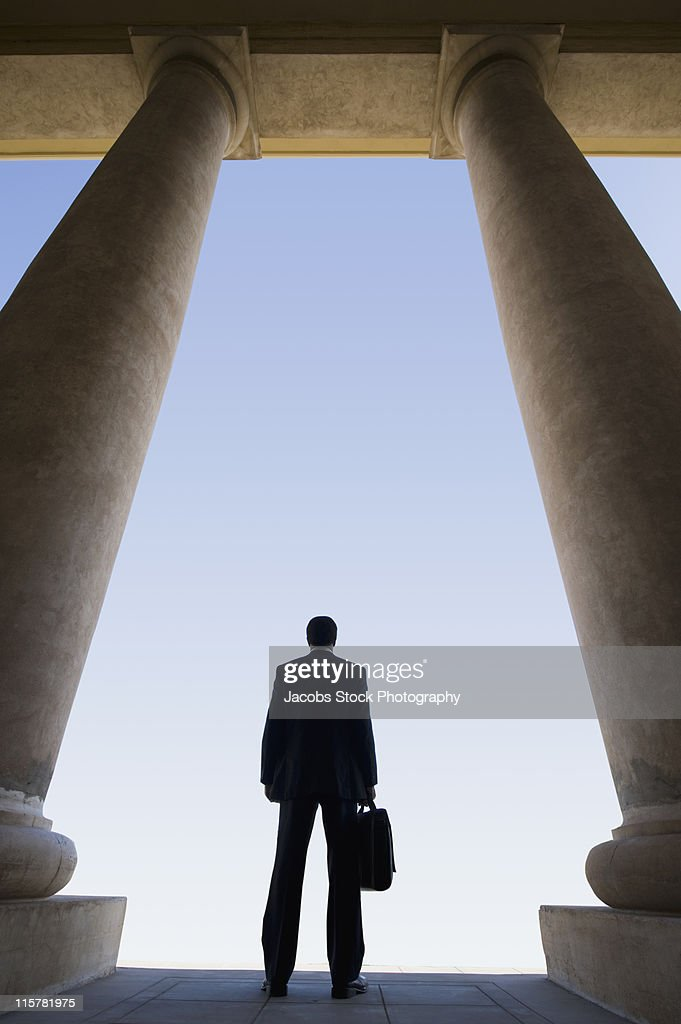 Businessman Standing Between Columns : Stock Photo