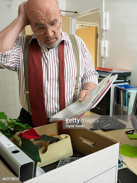 Businessman Standing by a Box and Holding Documents