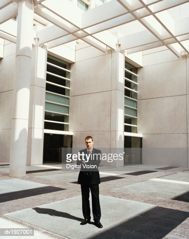 Businessman Standing by a Building With His Arms Crossed : Stock Photo