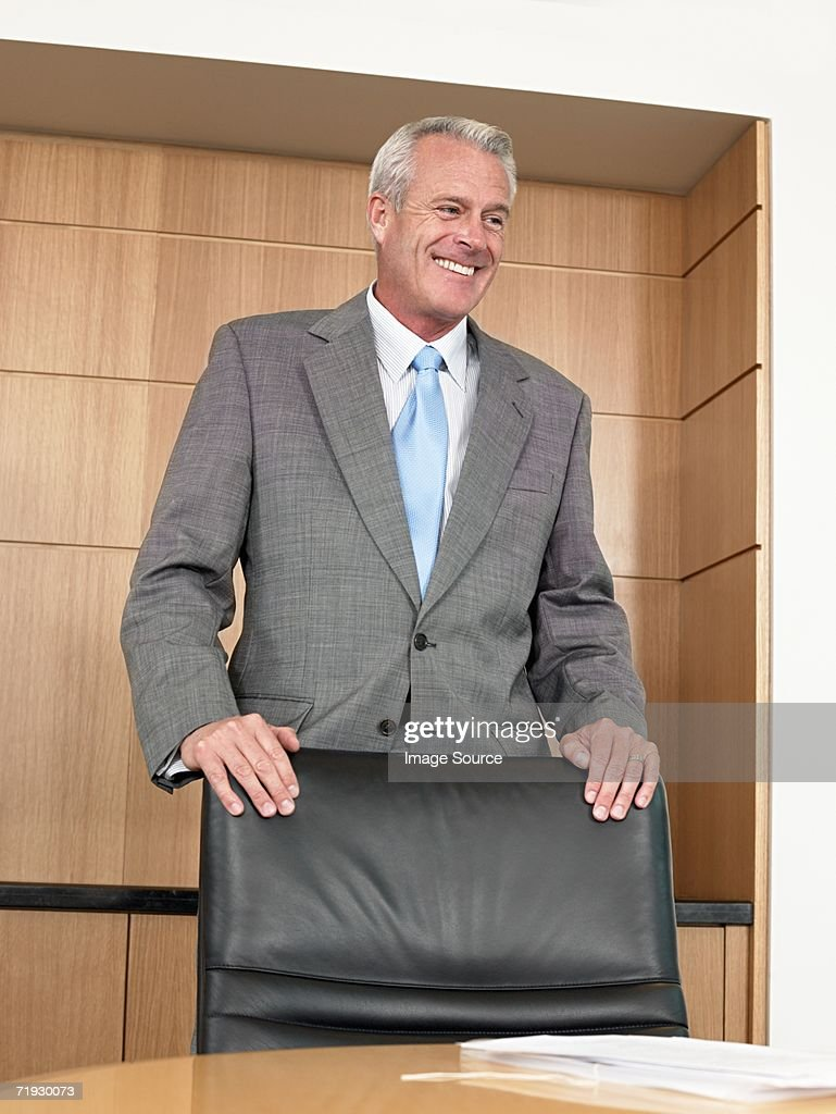 Businessman standing by chair : Stock Photo