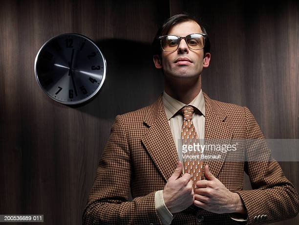 Businessman standing by clock holding lapels, portrait