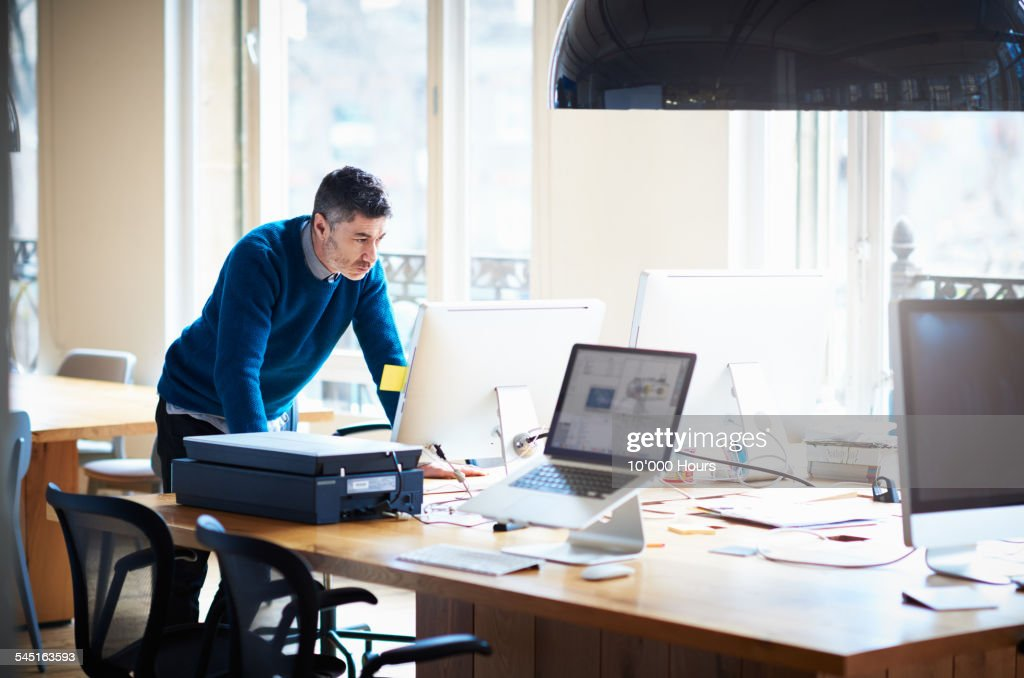 Businessman standing by desk working on a computer : Stock Photo