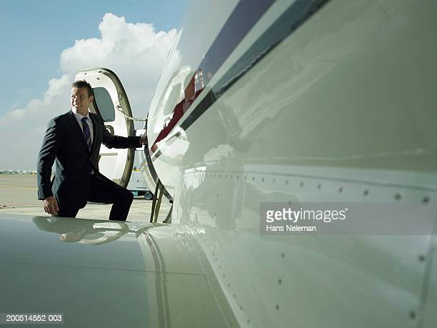 Businessman standing by door of private plane on airfield