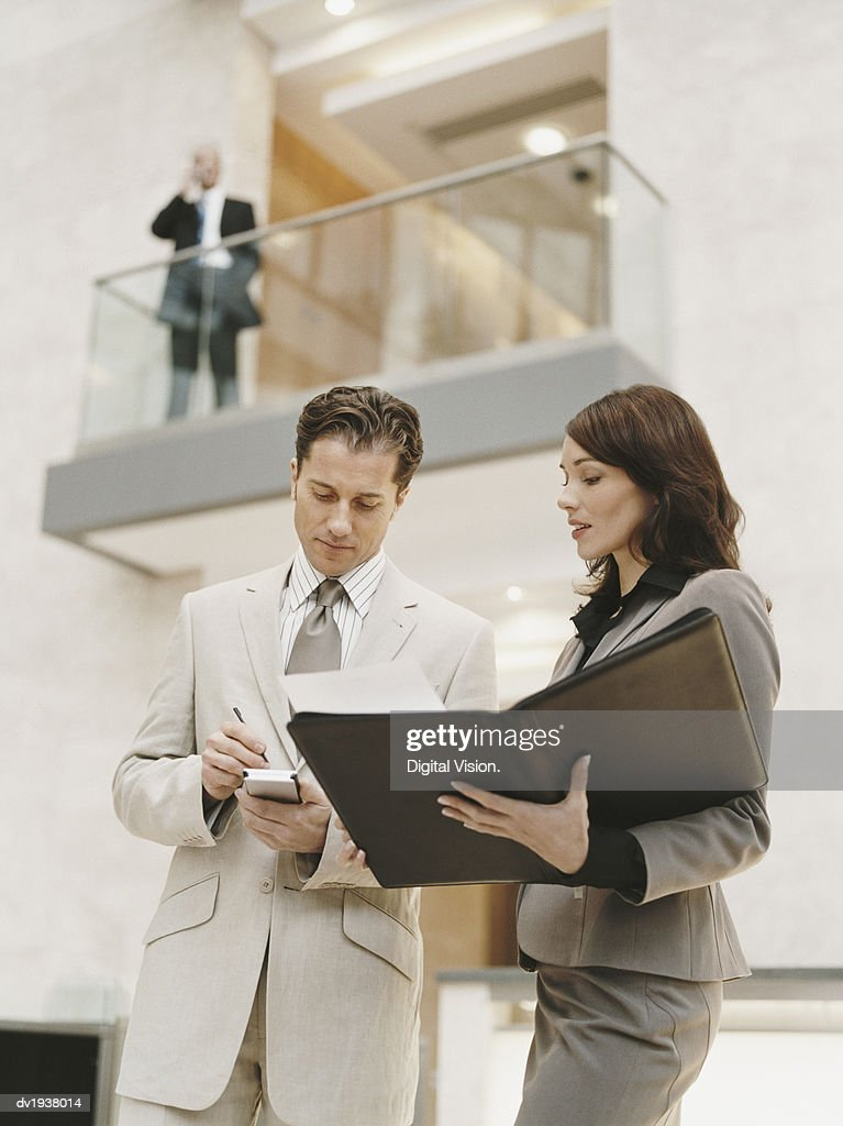 Businessman Standing by His Secretary and Writing in His Handheld PC