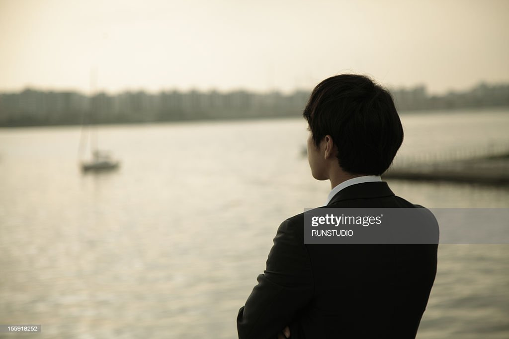 businessman standing by the river,rear view : Stock Photo