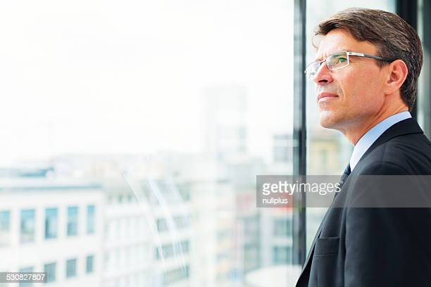 businessman standing by the window