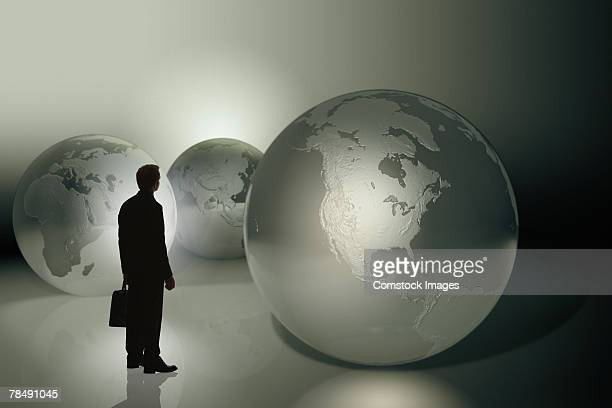 Businessman standing by three-dimensional world globes