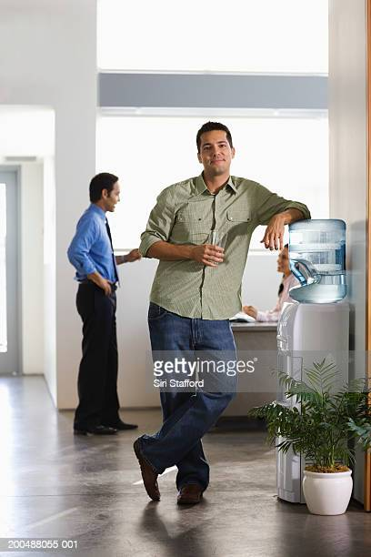 Businessman standing by water cooler in office