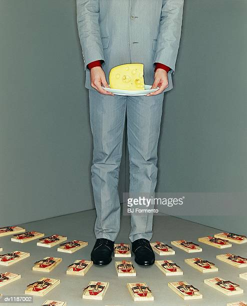 Businessman Standing Holding a Plate of Cheese Surrounded by Mousetraps