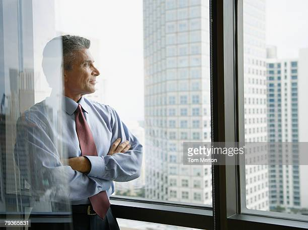 Businessman standing in a corridor by large windows
