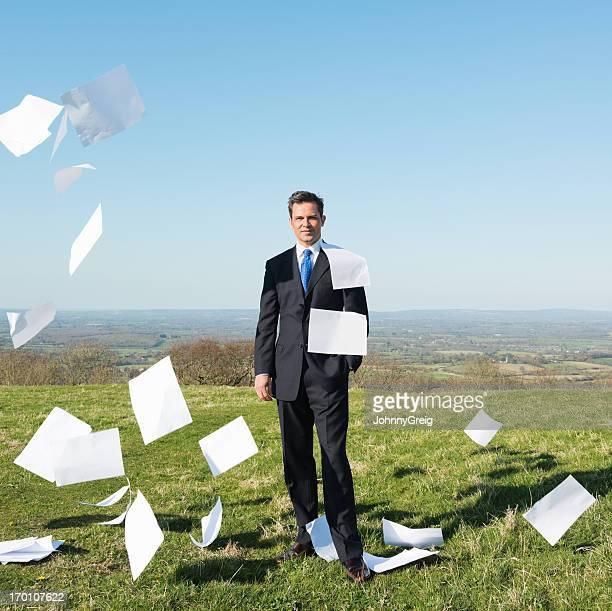 Geschäftsmann, stehen In einem Feld mit Flying Papierkram
