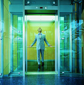 Businessman Standing in a Glass Elevator Looking Up