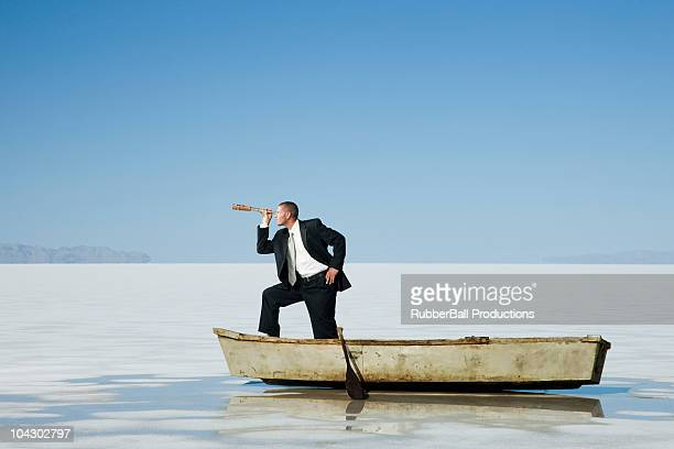 businessman standing in a row boat in the middle of nowhere holding a telescope
