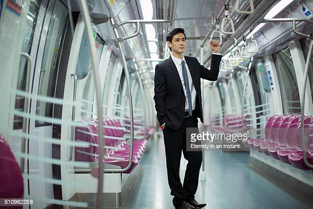 Businessman standing in a train car.