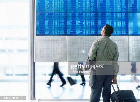 Businessman standing in airport, looking at flight schedule board