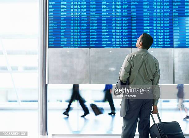 Businessman standing in airport, looking at flight schedule board