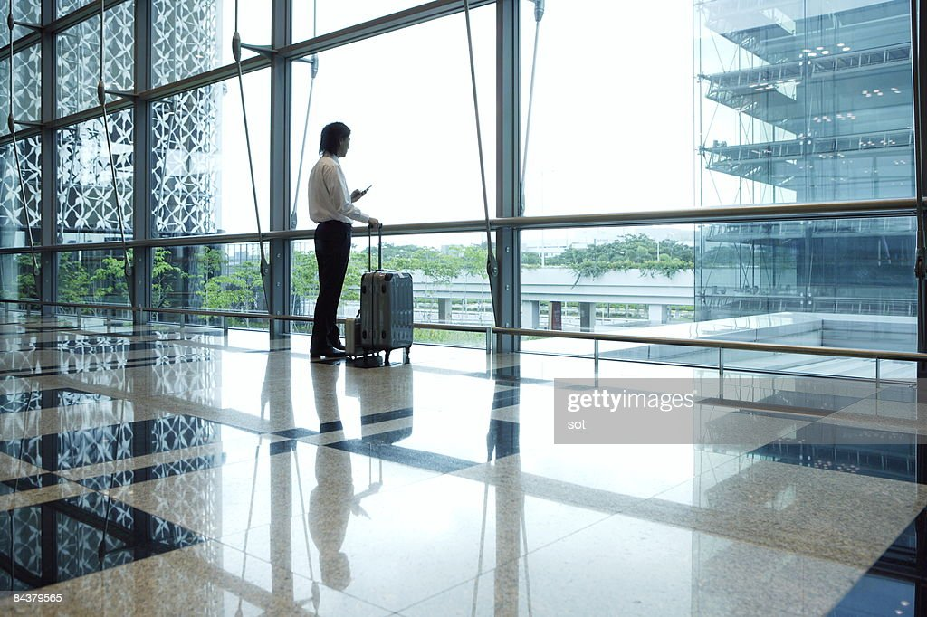 Businessman standing in airport using PDA : Stock Photo