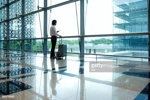 Businessman standing in airport using PDA