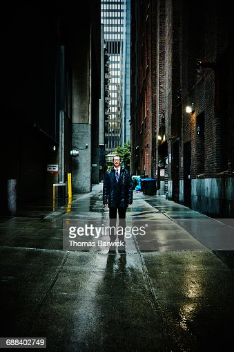Businessman standing in alley during rain storm