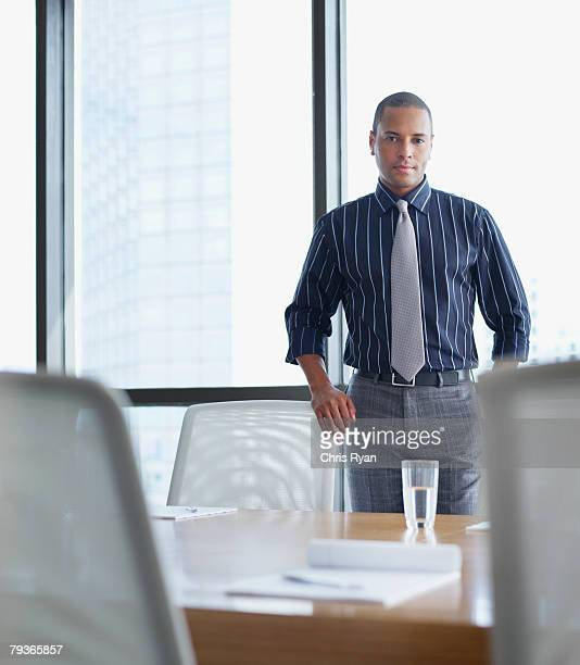 Businessman standing in boardroom by large windows