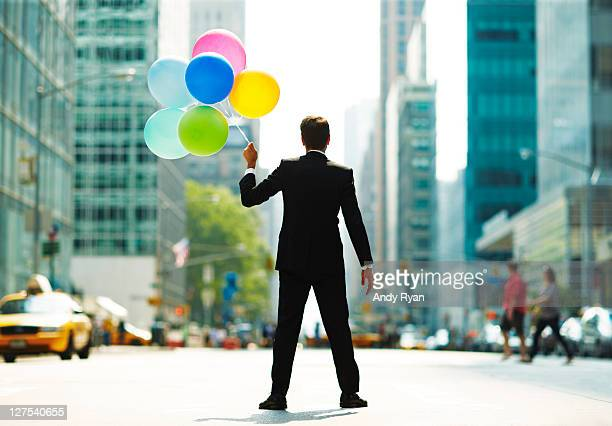 Businessman standing in city street with balloons.